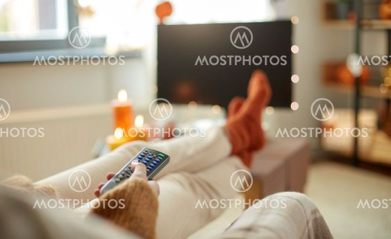 young woman watching tv at home on halloween