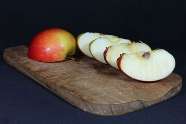 Red apple cut into different pieces on a wooden board...