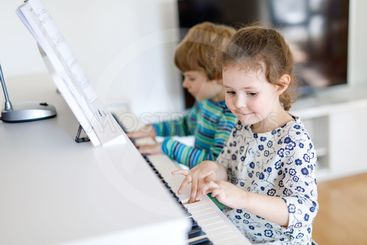 Two little kids girl and boy playing piano in living room...