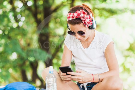 Young woman listening to the music on the smartphone