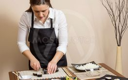 Portrait of woman chef cutting japanese sushi roll