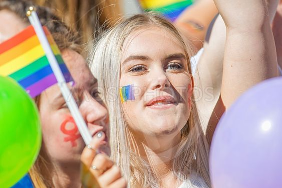 Young blond woman with the rainbow flag painted on cheek...