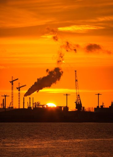 Industry, cranes, pollution and orange sunset