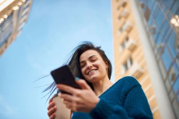 Smiling woman with smartphone is surrounded by tall...