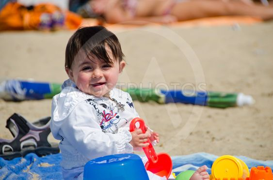 Baby Girl relaxing and playing on a Beach Towel