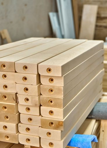 Joinery. Wooden table legs. Stacked wooden table legs in...