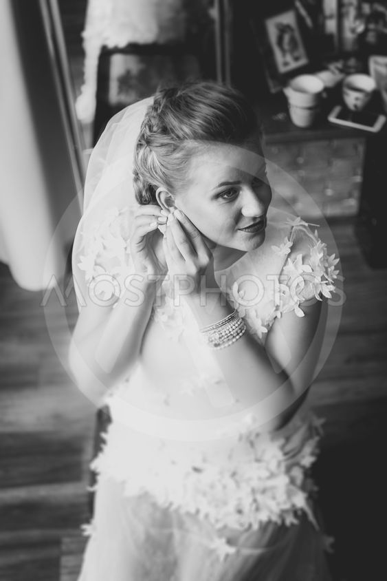 Black and white portrait of gorgeous bride putting on...