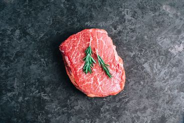 Raw beef steak on black background with rosemary, top view.