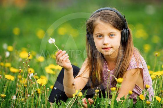 Cute little girl in headphones enjoying music in nature.