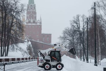 A small loader excavator bobcat removes snow from the...
