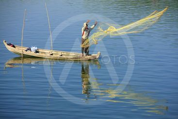Local man fishing with a net from a boat, Amarapura,...