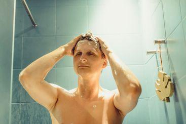 Close up young caucasian man washing hair during shower...