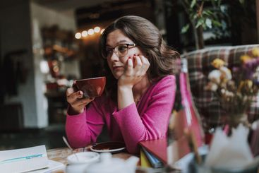 Calm young woman sitting in coffee shop