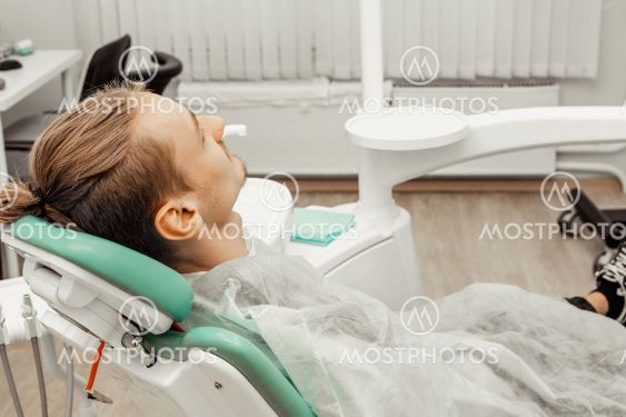A young and satisfied male patient in the dentist's...