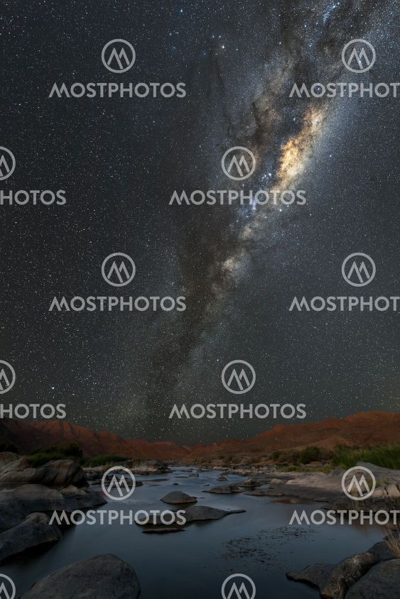 A vertical night sky landscape with the Milky Way and a...