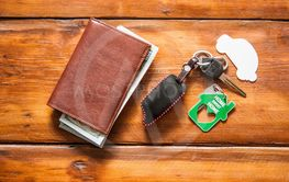 leather wallet and car key on wood table with dollar bills