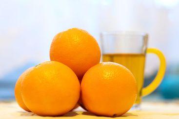 A cup of orange tea and fresh, ripe, juicy oranges