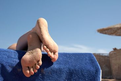 Foot of the girl sunbathing on a beach
