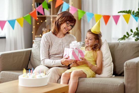 grandmother giving granddaughter birthday gift
