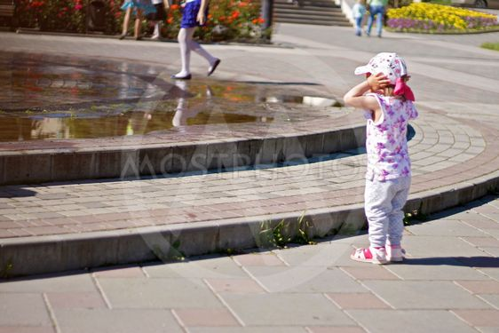 Baby near a splashing fontain in the center of town 12...
