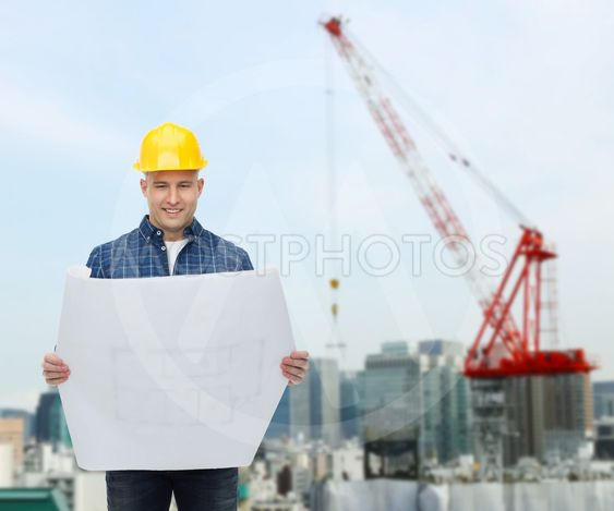 smiling male builder in helmet with blueprint