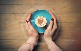photo of female hands holding cup of coffee on the...