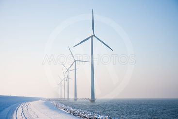 Row of snowy windmills standing in Dutch sea disappearing...