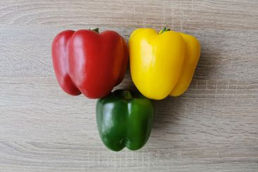 Three fresh sweet peppers in red, yellow and green colors