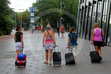 4 women with suitcases
