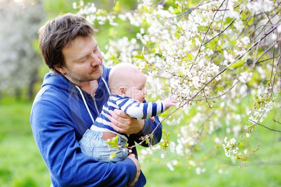 Little baby with father in the blossom garden