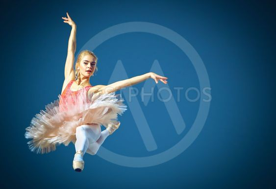 Beautiful female ballet dancer on a grey background....
