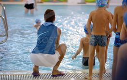 Children swimming competition in pool, relay race