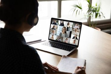 Back view of woman worker engaged in online team meeting