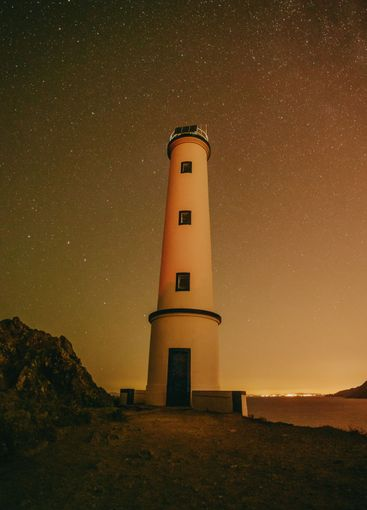 A white lighthouse with a sky filled with stars as a...
