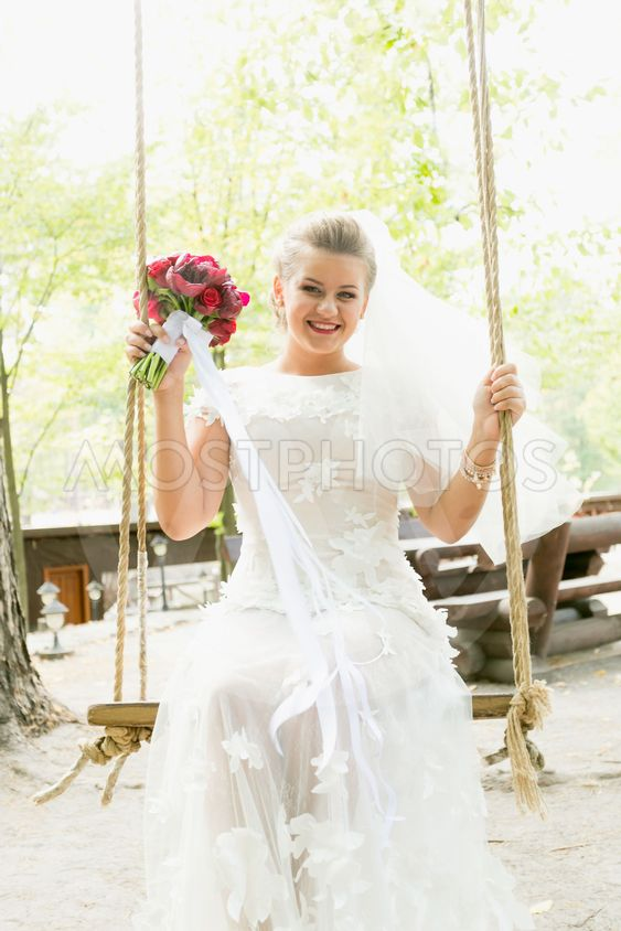 Toned portrait of beautiful bride swinging on swing at park