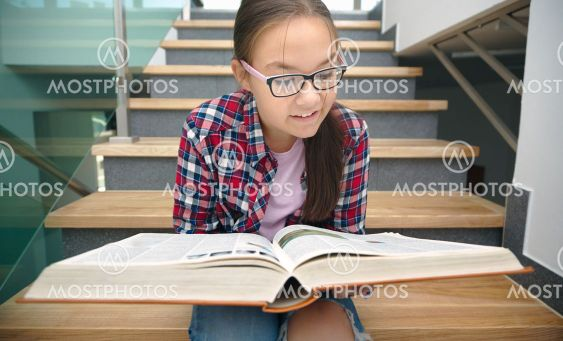 Girl is reading book while sitting on stairs