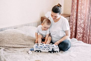 pregnant Mother playing with her baby boy with cars