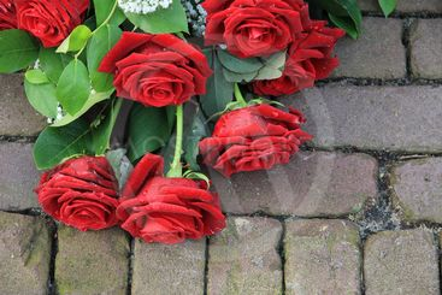 Red rose sympathy flower arrangement on pavement