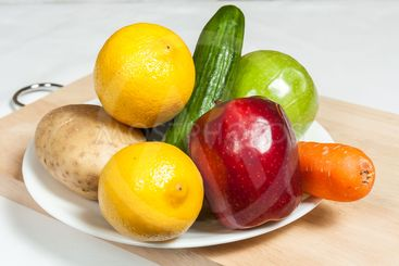 Plate of fruits and vegetables on chopping board