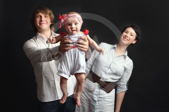Parents hold their baby studio