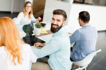Portrait of  young bearded  businessman and his team