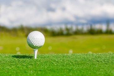 Landskap med golfboll på en peg på tee.