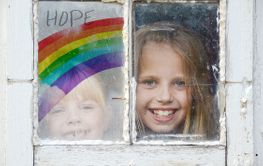 little girls in window with rainbow sign