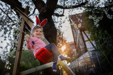 Happy beautiful little toddler girl with red Easter...