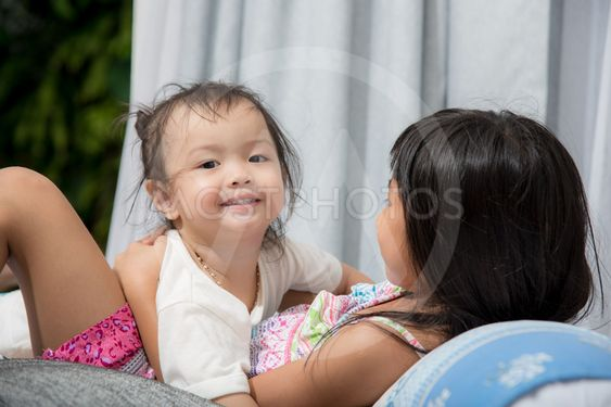 Cute Asian girl playing with her sister on bed at home.
