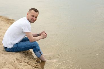 Lonely smiling man sitting on a beach by the river