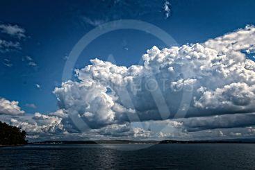 White Cumulus cloud in blue sky at sea.