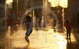 Happy kids have fun playing in city water fountain