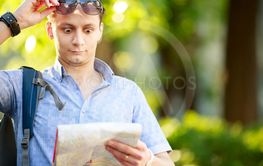 Young man with a map outdoors