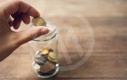 Business men Put the coin in a glass jar To save money,...